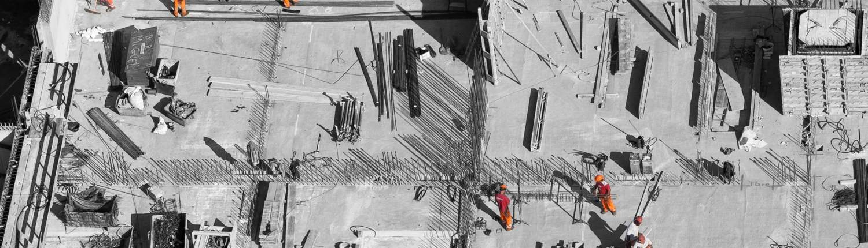 Ansatte i orange arbeidsdresser på byggeplass. Protan velger Sariba.