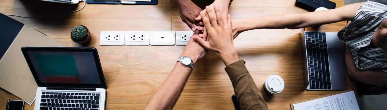Armer som holdes over et arbeidsbord. Vil du bli vår nye kollega?