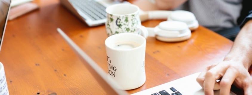 Mennesker som jobber ved siden av hverandre ved et spisebord. Valg av HR-Teknologi.