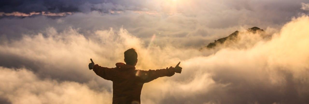 Mann holder tomlene i været foran skyer. Sertifisert i SuccessFactors Employee Central