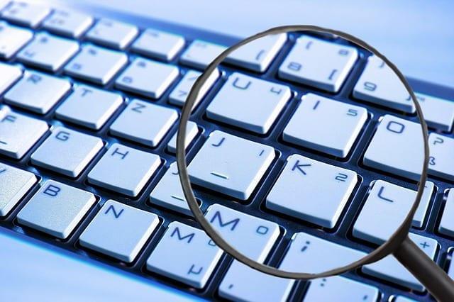 Forestørrelsesglass over tastatur. Sariba HR Data Protection Controll