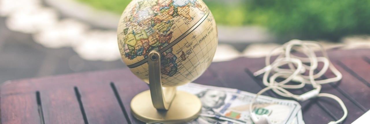 Globus og penger på et bord. Feriepenger opptjent i utland.