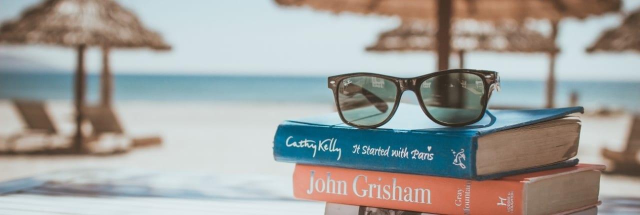 Bøker og solbriller foran havet og parasoller. engasjement og samarbeid