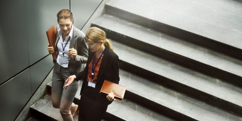 To personer går ned en trapp mens de snakker
