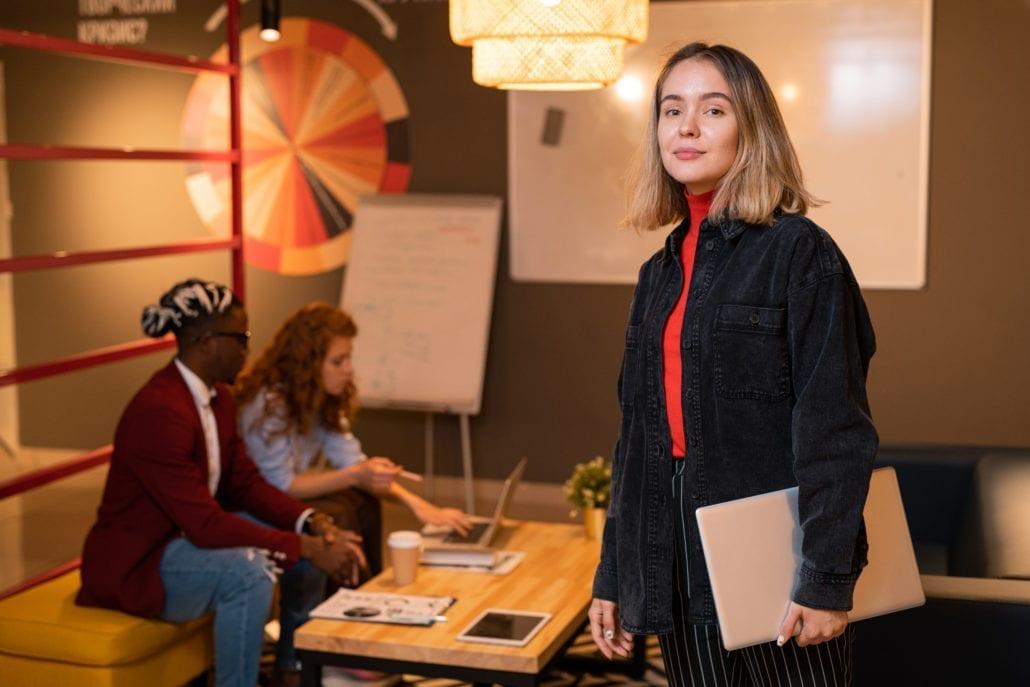 Jente poserer foran et skrivebord