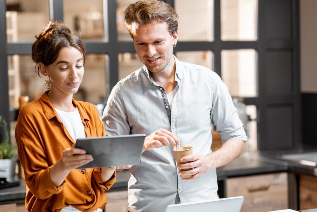 Man and woman peeking at a tablet