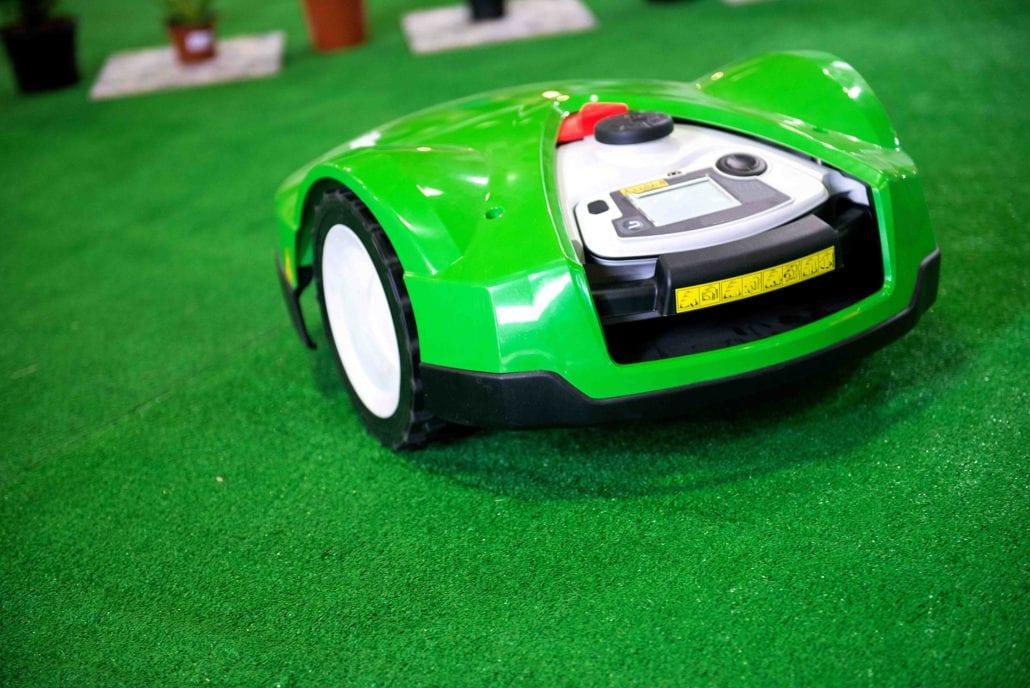a robotic lawn mower working on a green grass fiel YRECT5F